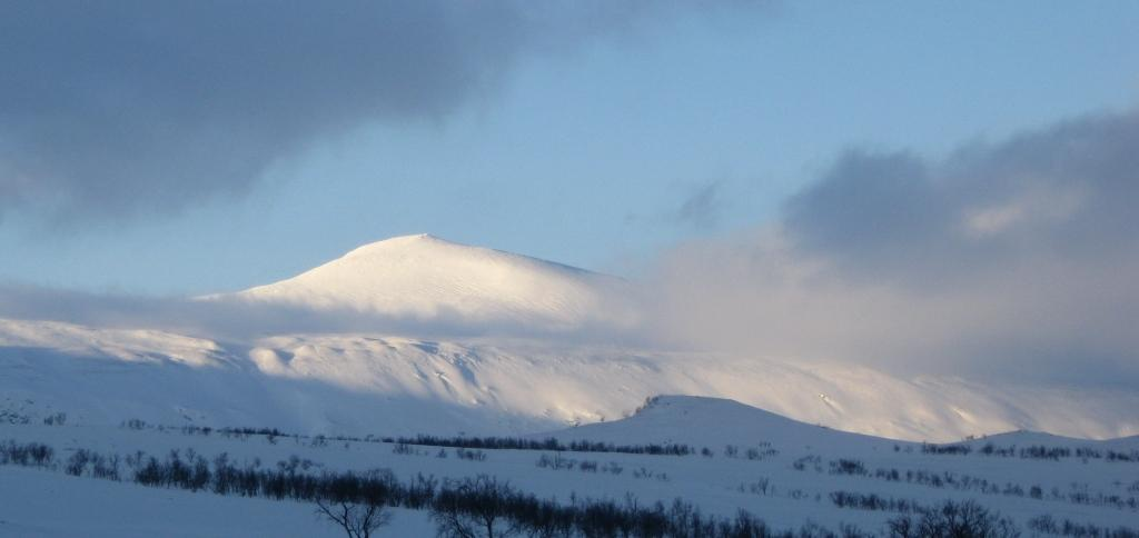 Måskostjåhkkå at 1420m catches sun and beckons to be skied.